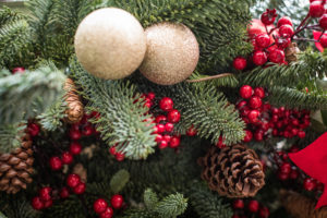 Decorated Christmas tree. Bright decorations for the New Year. Christmas decoration. Gold balls, red berries and ribbons, cones decorate the Christmas tree. Christmas decoration. Background for New Year's greetings.